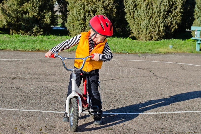 安全渡过他的自行车的逗人喜爱的小男孩 库存照片