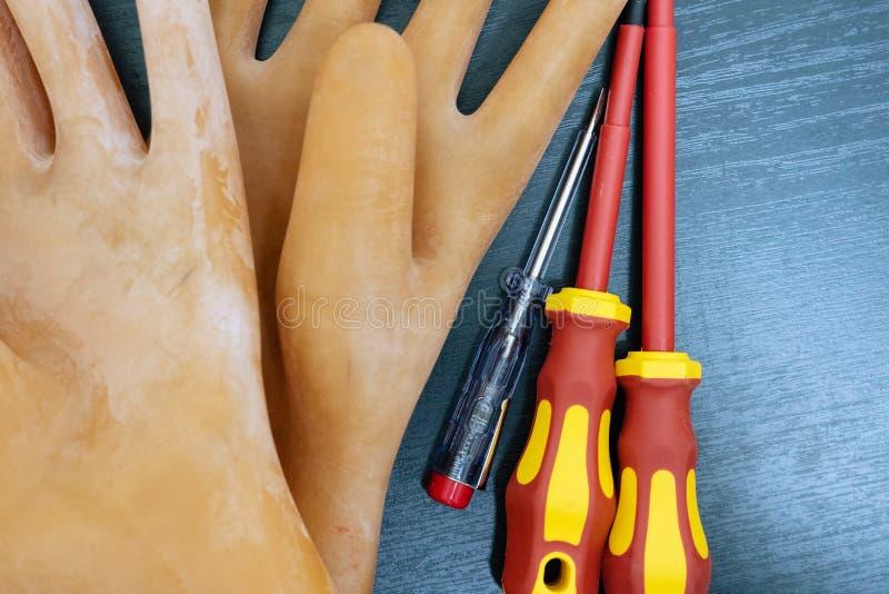 安全的橡胶手套与电子设施一起使用和的三把螺丝刀与电子接线一起使用 免版税库存照片