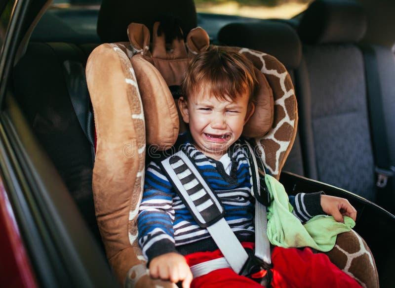 安全矿车位子的哭泣的男婴 免版税库存图片