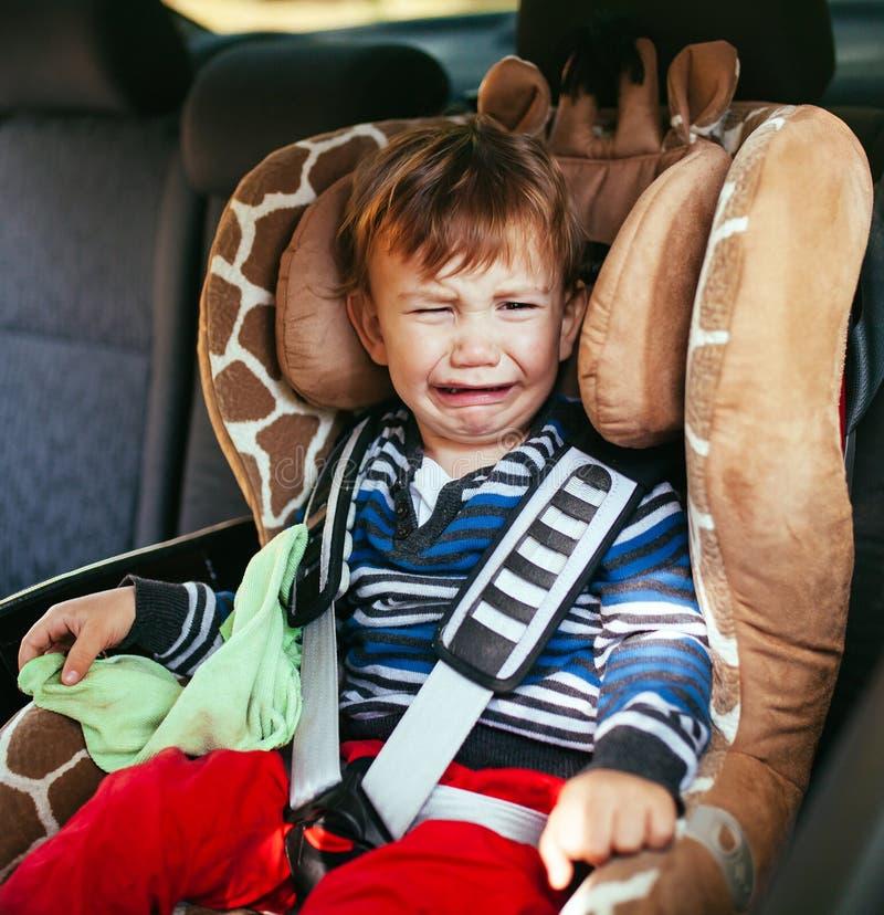 安全矿车位子的哭泣的男婴 库存照片