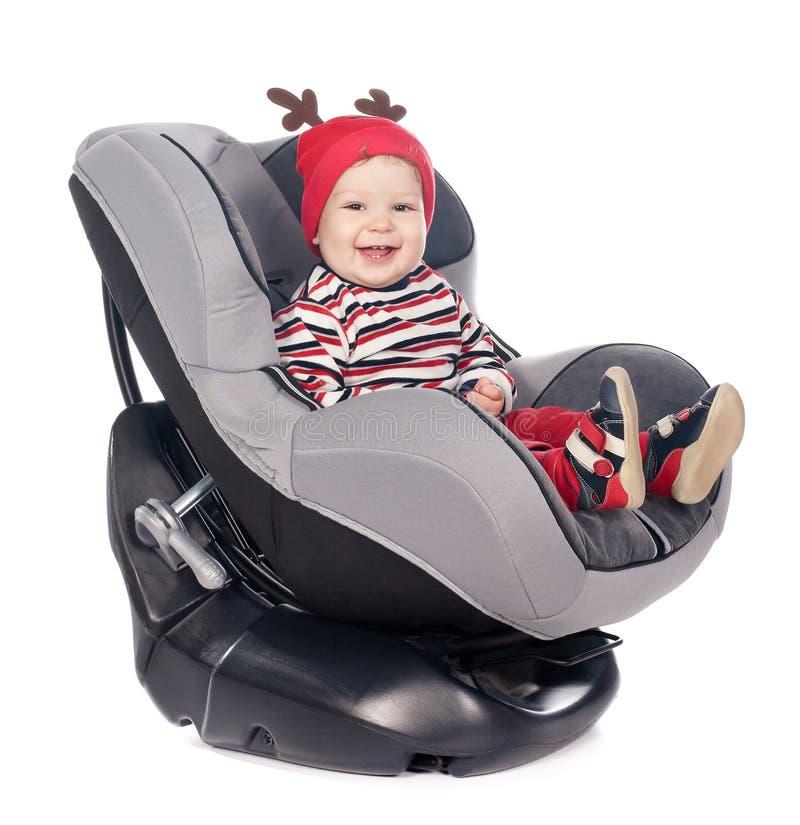 安全矿车位子的逗人喜爱的男婴在白色 免版税库存图片