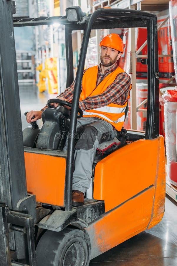 安全背心的男性坐在铲车机器的工作者和盔甲 图库摄影