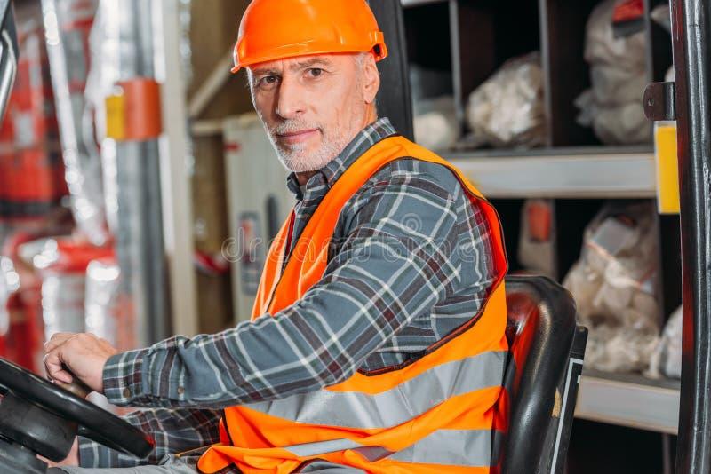 安全背心的资深坐在铲车机器的工作者和盔甲 库存图片