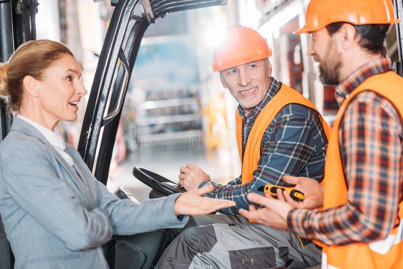 安全背心的资深工作者和盔甲坐在铲车机器和谈话与同事 图库摄影