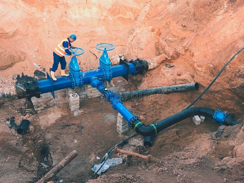 安全衣裳的工作者驾驶在城市饮用水管子的阀门输送管道 库存照片