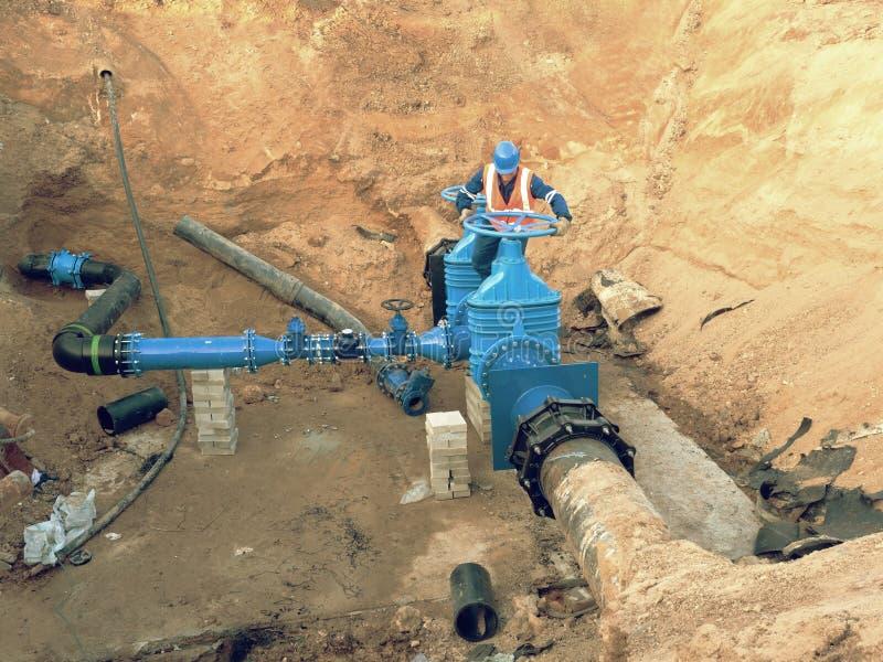 安全衣裳的工作者驾驶在城市饮用水管子的阀门输送管道 免版税图库摄影