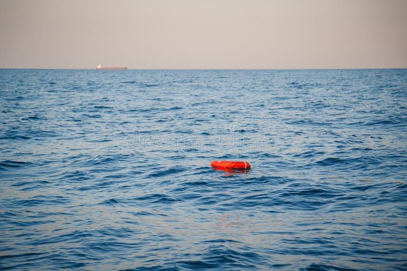 安全设备、救生圈或者抢救浮体圆环与漂浮在蓝色海的绳索抢救人 乘快艇,海洋背景 库存图片