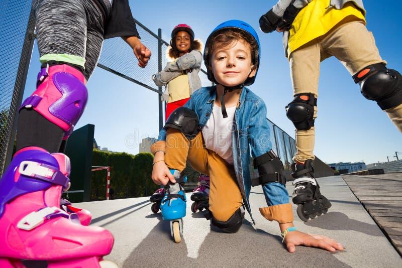 安全齿轮的逗人喜爱的男孩在户外溜冰鞋 库存图片