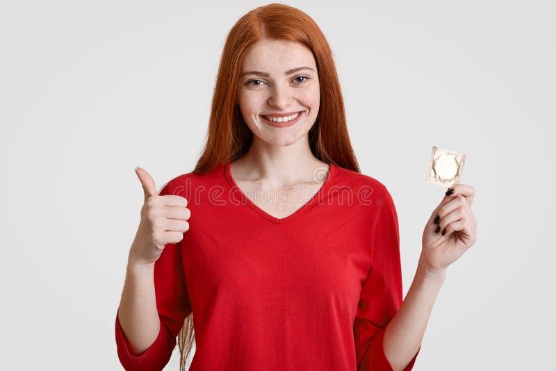安全pleaure和保护概念 有有雀斑的皮肤的高兴的红发女性在红色衣裳拿着避孕套,显示好标志,穿戴, 库存照片