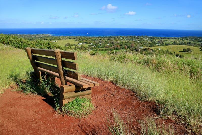安加罗阿和太平洋的有在红色金属渣的一个长木凳的在普纳岛波城火山,复活节岛,智利观点 免版税库存图片