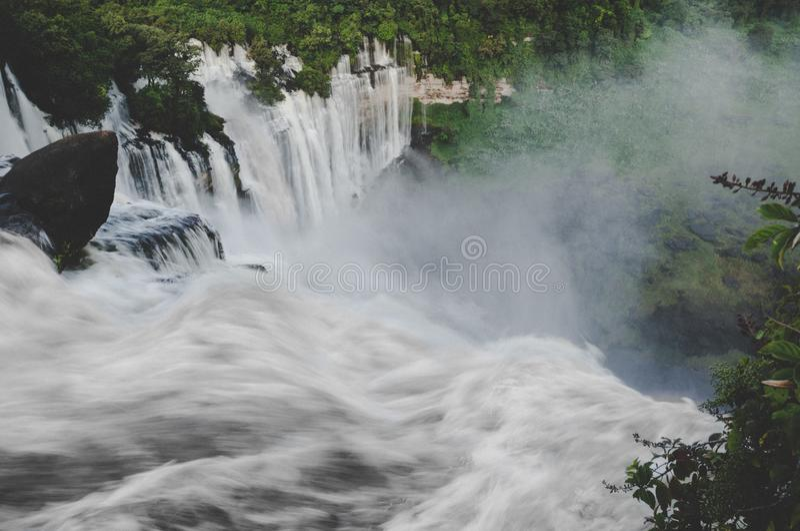 安哥拉的Kalandula瀑布满流的与豪华的绿色雨林、岩石和浪花,非洲 图库摄影