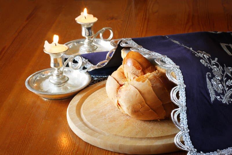 安息日图象。鸡蛋面包面包和坎德拉在木桌上 免版税库存图片