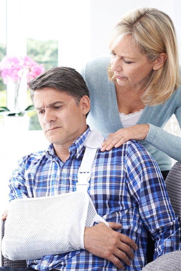 安慰丈夫的妻子遭受以胳膊伤 免版税图库摄影