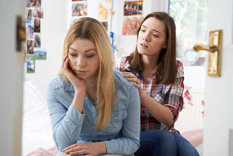 安慰不快乐的朋友的十几岁的女孩在卧室 免版税库存图片