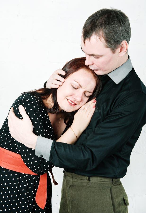安慰他哭泣的妇女的人 免版税库存照片