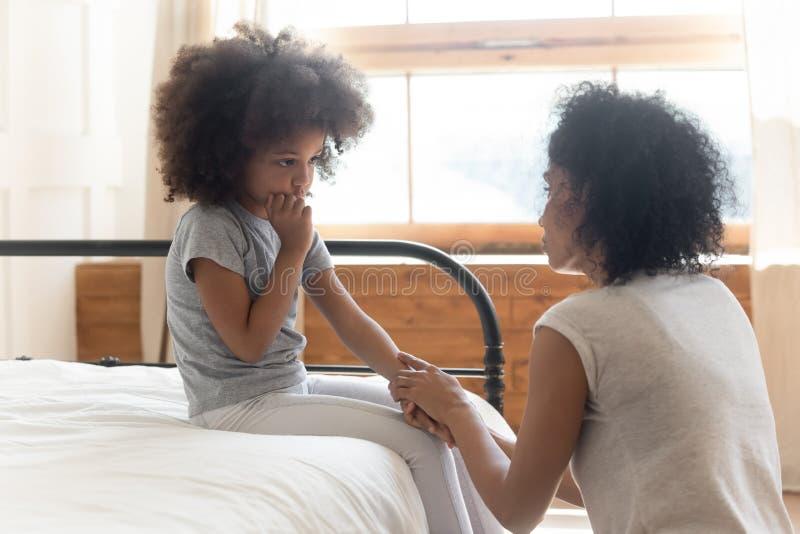 安慰哀伤的矮小的女儿的担心的非洲母亲藏品手 库存图片