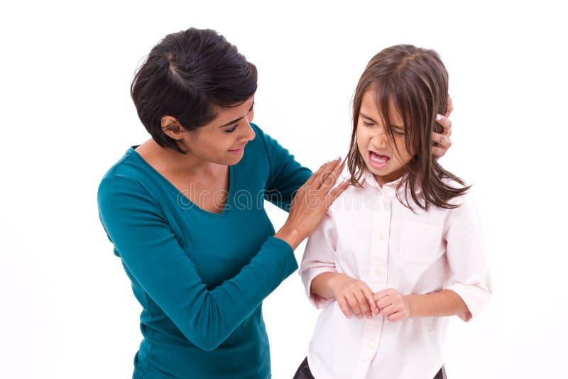 安慰哭泣的女儿的母亲 免版税库存图片