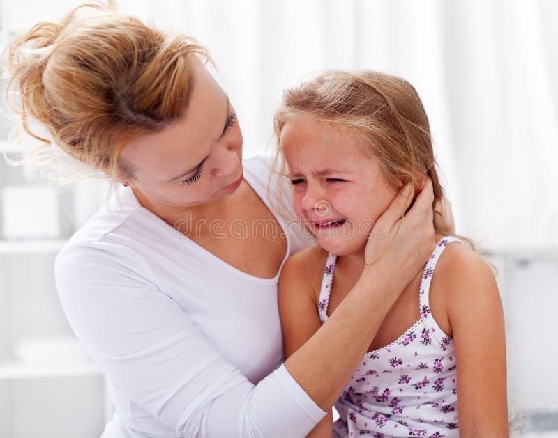 安慰哭泣的女孩她的小母亲 库存照片