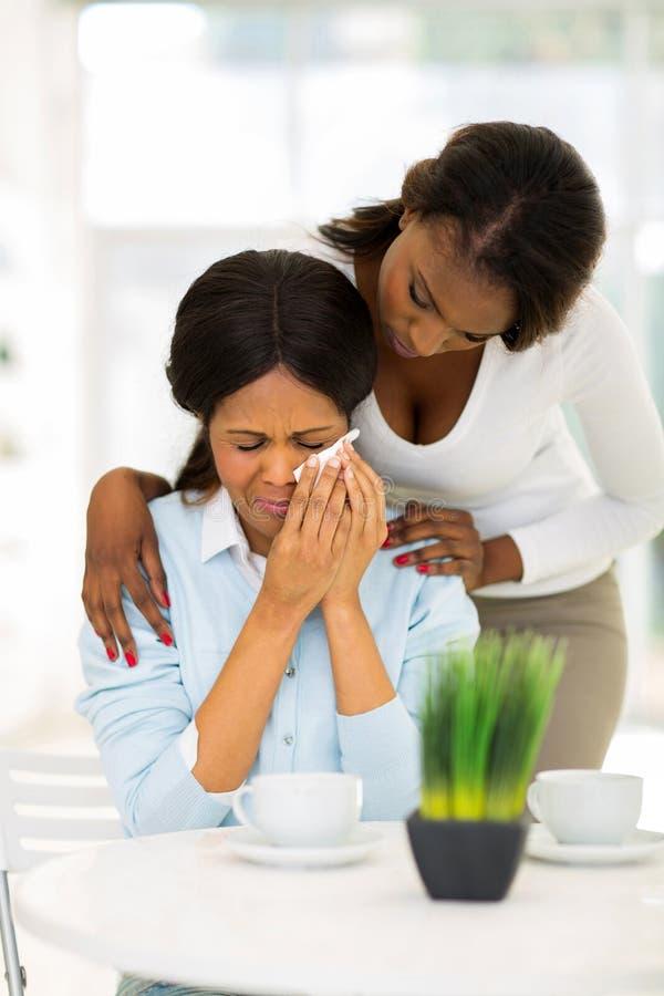 安慰哭泣的母亲的非洲妇女 免版税图库摄影