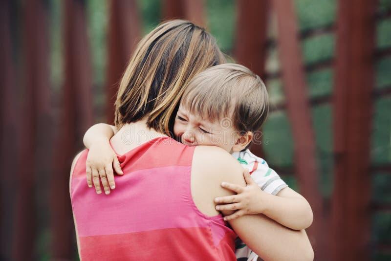 安慰她哭泣的小小孩男孩儿子的妇女母亲 图库摄影