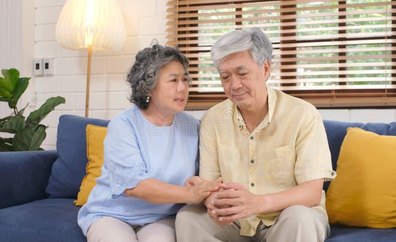 安慰她的从沮丧的情感的资深亚裔妇女丈夫,当在家坐沙发客厅,老退休时 免版税图库摄影
