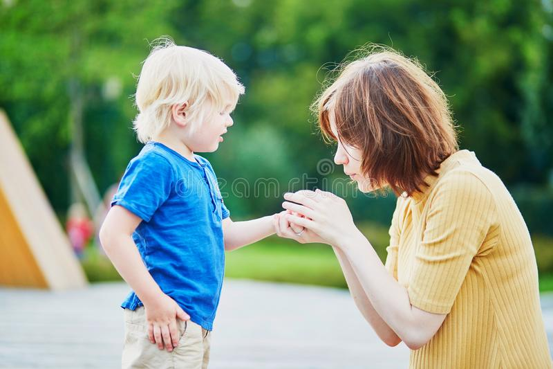 安慰她的儿子的母亲,在他他的手受伤后 免版税库存照片