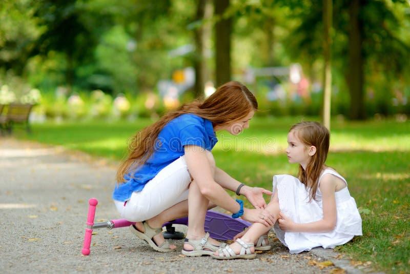 安慰她的女儿的母亲,在她跌倒了后,当乘坐她的滑行车时 库存照片