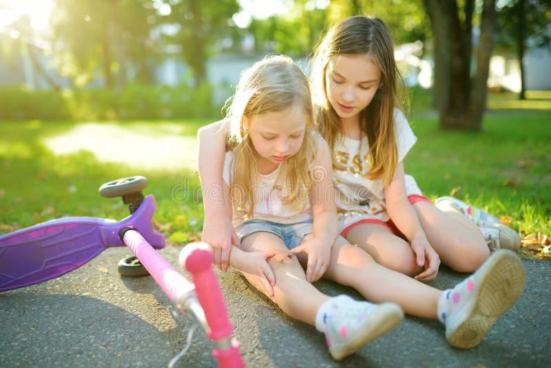 安慰她的妹的可爱的女孩,在她跌下她的滑行车在夏天公园后 受到伤害的孩子,当乘坐反撞力时 免版税图库摄影