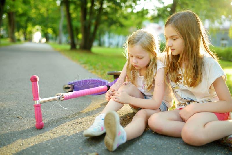 安慰她的妹的可爱的女孩,在她跌下她的滑行车在夏天公园后 受到伤害的孩子,当乘坐反撞力s时 免版税库存图片