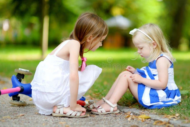 安慰她的姐妹的小女孩,在她跌倒了后,当乘坐她的滑行车时 图库摄影
