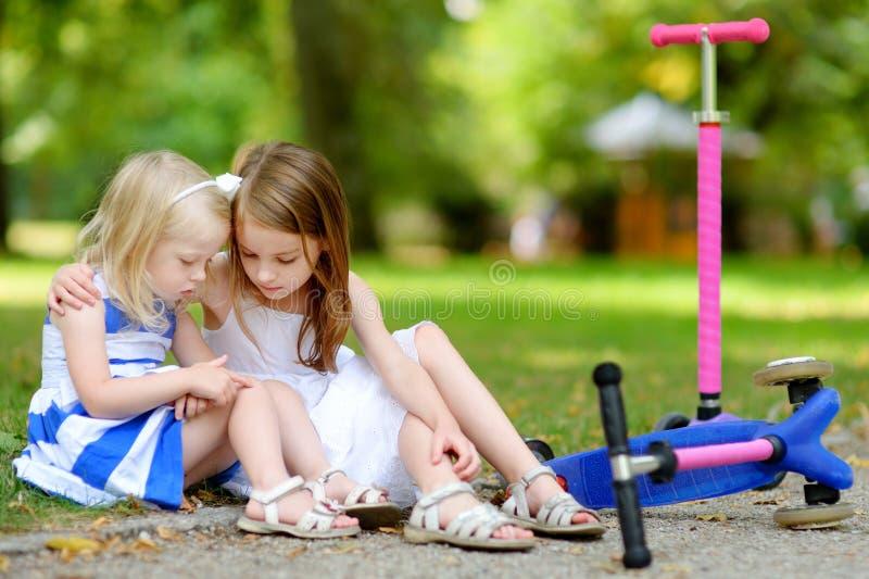 安慰她的姐妹的小女孩,在她跌倒了后,当乘坐她的滑行车时 免版税库存图片