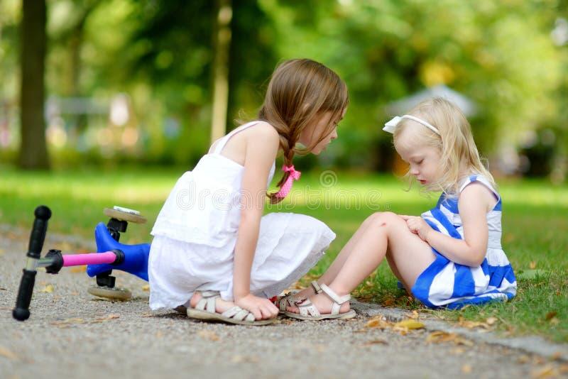 安慰她的姐妹的小女孩,在她跌倒了后,当乘坐她的滑行车时 免版税库存照片