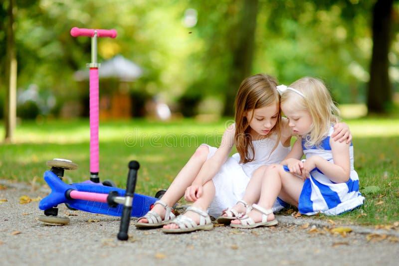 安慰她的姐妹的小女孩,在她跌倒了后,当乘坐她的滑行车时 库存图片