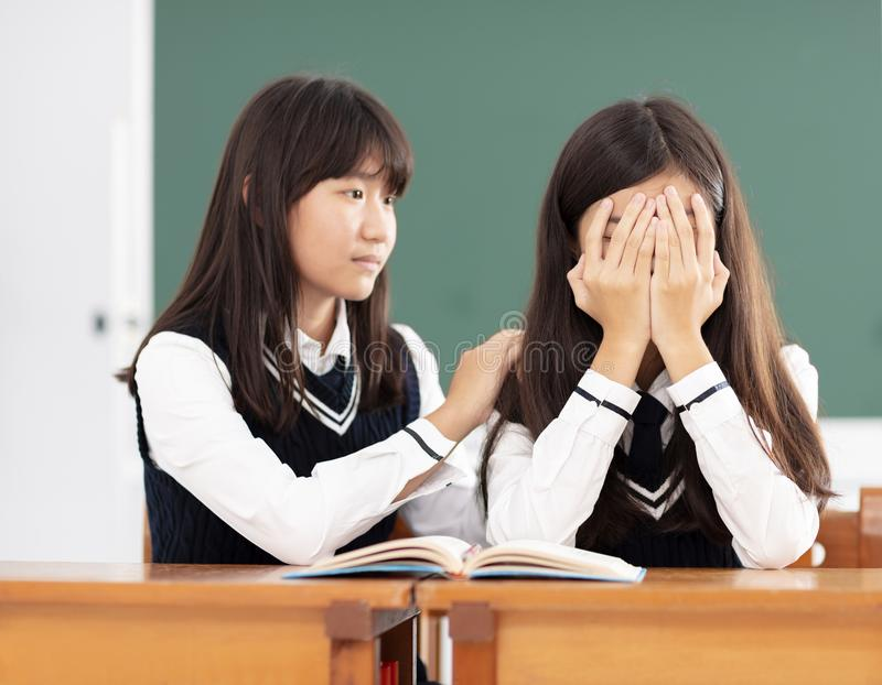 安慰对哀伤的学生的朋友在教室 库存照片