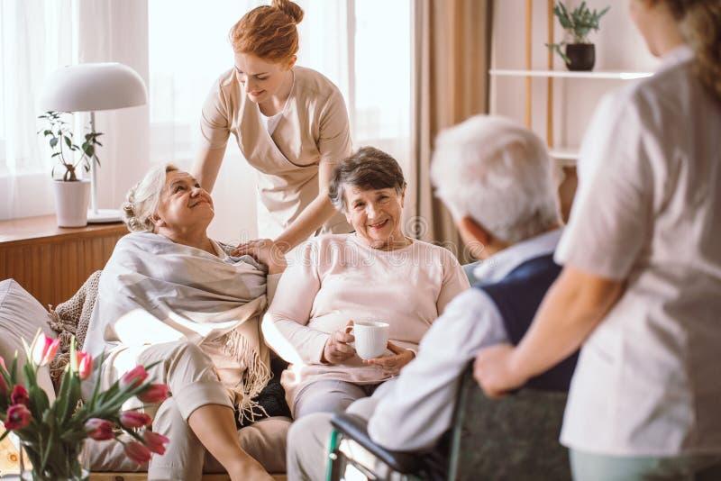 安慰年长妇女的年轻照料者在老人院 免版税库存照片