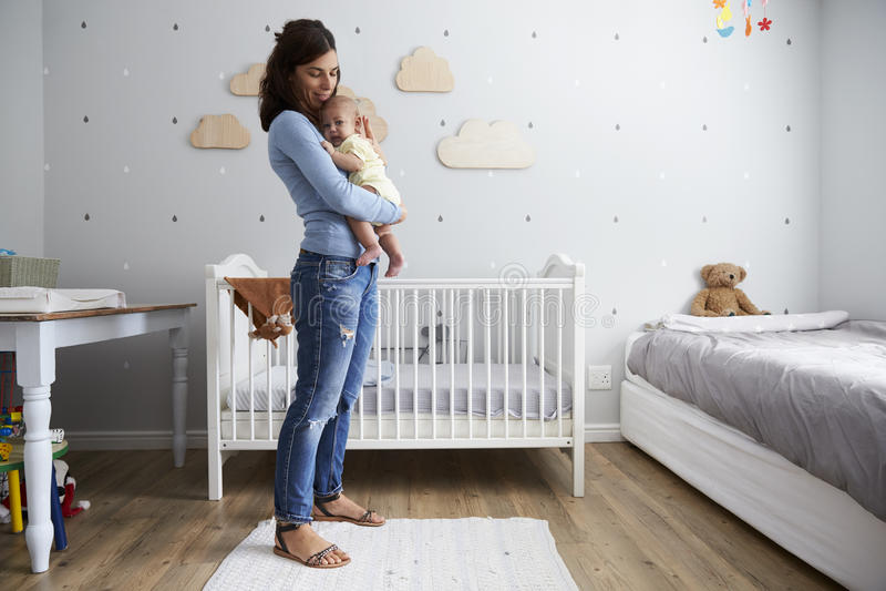 安慰新出生的小儿子的母亲在托儿所 免版税库存照片
