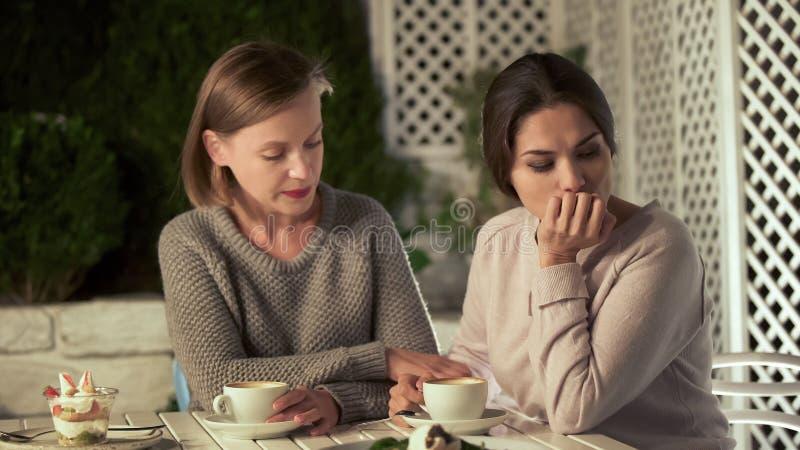 安慰生气朋友的少女,食用在大阳台,友谊支持的咖啡 免版税库存照片