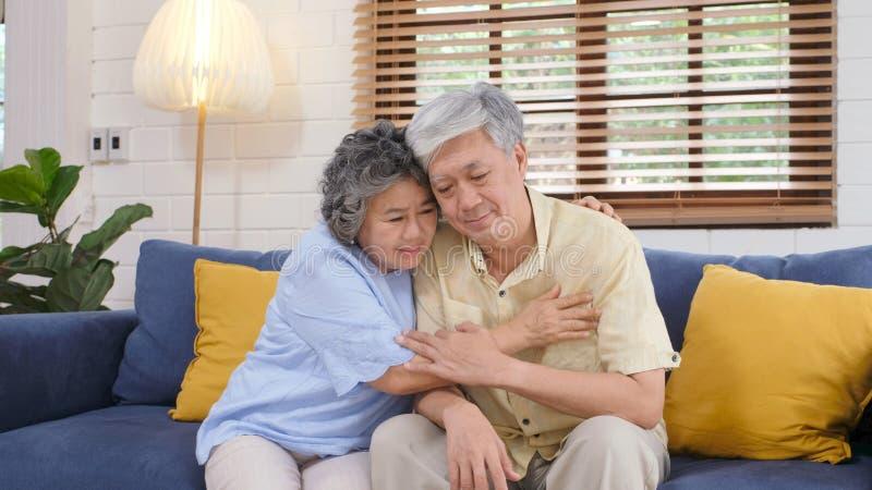 安慰的资深亚洲夫妇从沮丧的情感,当在家坐沙发客厅,老退休时 免版税库存照片