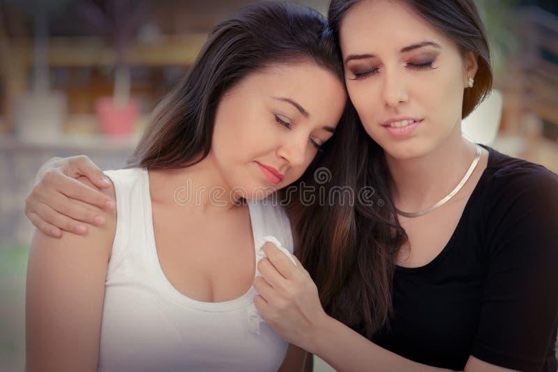 安慰眼泪汪汪的朋友的少妇 免版税库存图片