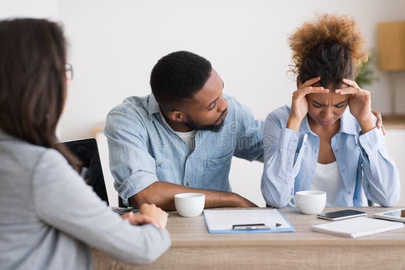 安慰绝望妻子的非裔美国人的丈夫哭泣在家庭建议 库存图片