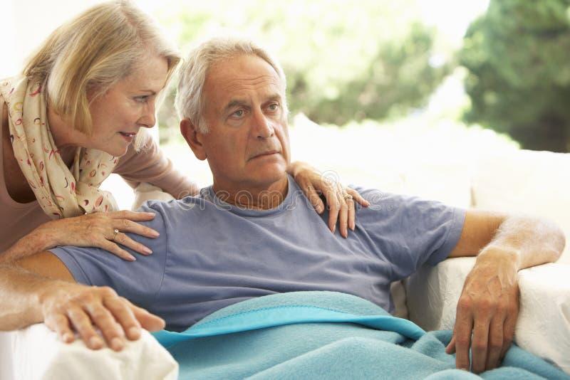 安慰老人的妻子感觉不适休息在毯子下 库存图片
