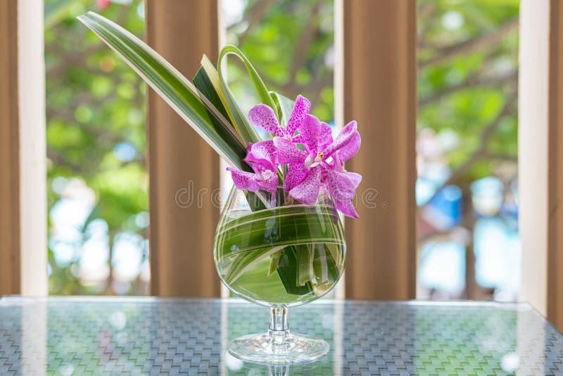 安排在一个玻璃花瓶的兰花在海滩东方好客大气 免版税图库摄影