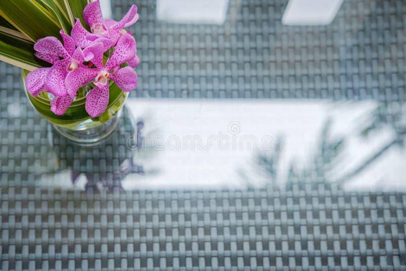 安排在一个玻璃花瓶的兰花在海滩东方好客大气 免版税库存照片