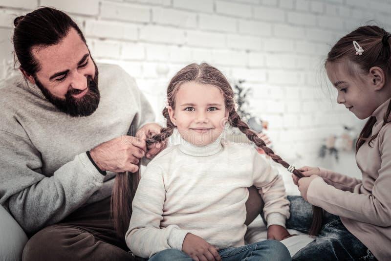 安排小逗人喜爱的女孩她的头发编辫子由姐妹和父亲 免版税库存照片