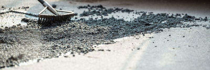安排新鲜的沥青混合物的犁耙的宽看法图象 免版税库存图片