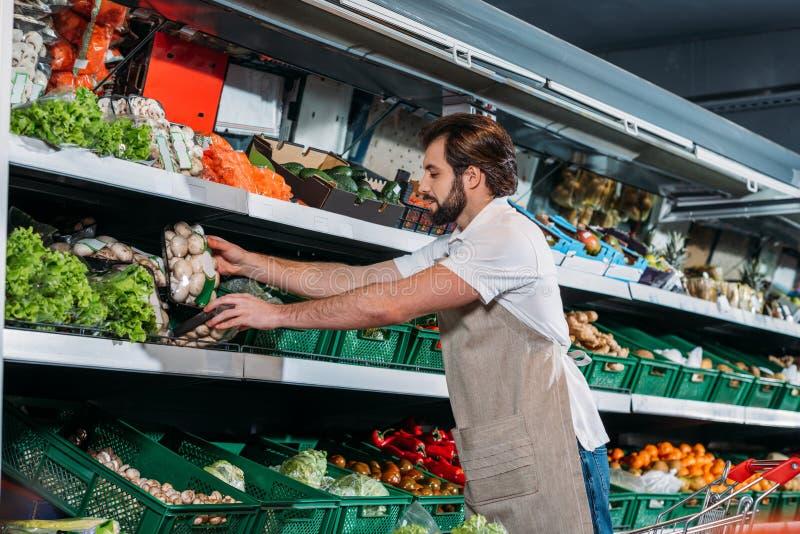 安排新鲜蔬菜的围裙的男性售货员 库存图片