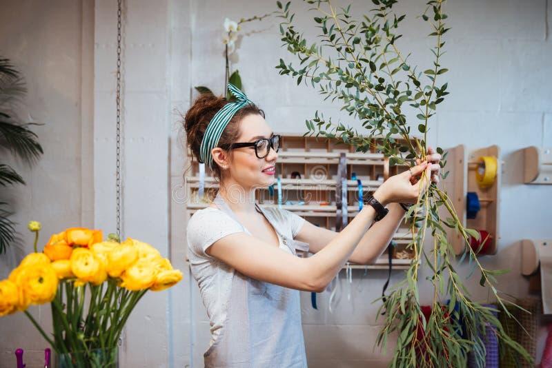 安排植物的微笑的可爱的少妇卖花人 库存图片