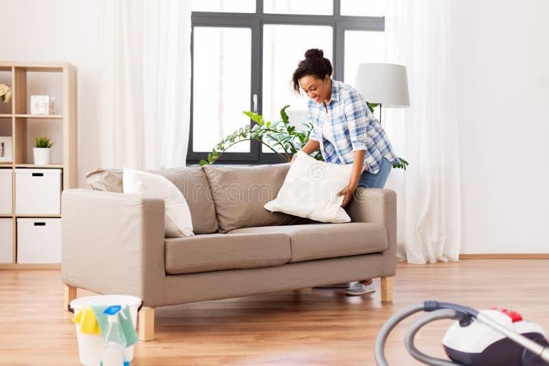 安排沙发坐垫的非裔美国人的妇女 免版税库存照片