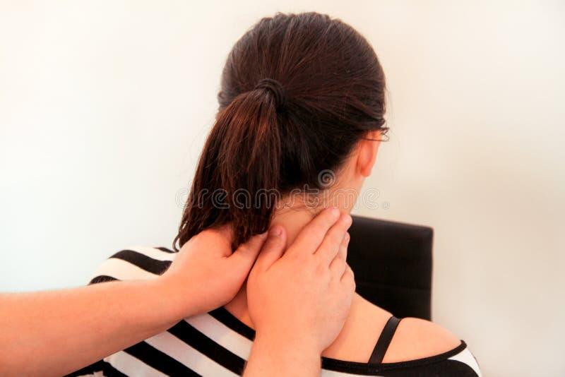 安排的妇女她的脖子按摩由生理治疗师 免版税库存图片