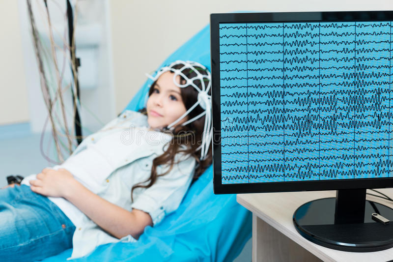 安排的小女孩她的脑波被记录通过脑电描记器 免版税库存照片